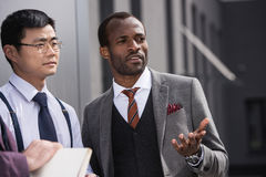 Young thoughtful multiethnic businessmen in formalwear talking outdoors,. Business team meeting Royalty Free Stock Photo