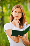 Young thoughtful woman holding book Stock Photos
