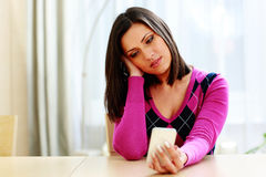 Young thoughtful woman holding smartphone Royalty Free Stock Image