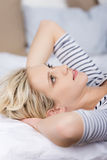 Young Thoughtful Woman Lying On Bed. Thoughtful woman with hands behind head lying on bed Stock Image