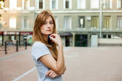 Young thoughtfull redhead woman walking around city Royalty Free Stock Photo