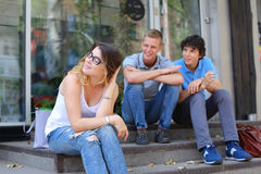 Young three friends sitting floor in the street, talking, using. Three friend female male sitting on the doorstep floor cafe, chatting, talking, using technology Royalty Free Stock Photo