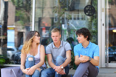 Young three friends sitting floor in the street, talking, using. Three friend female male sitting on the doorstep floor cafe, chatting, talking, using technology Royalty Free Stock Image