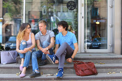 Young three friends sitting floor in the street, talking, using. Three friend female male sitting on the doorstep floor cafe, chatting, talking, using technology Royalty Free Stock Images