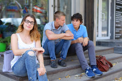Young three friends sitting floor in the street, talking, using. Three friend female male sitting on the doorstep floor cafe, chatting, talking, using technology Stock Photo