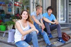 Young three friends sitting floor in the street, talking, using. Three friend female male sitting on the doorstep floor cafe, chatting, talking, using technology Stock Photography