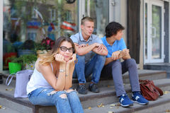 Young three friends sitting floor in the street, talking, using. Three friend female male sitting on the doorstep floor cafe, chatting, talking, using technology Stock Photos