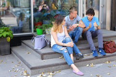 Young three friends sitting floor in the street, talking, using. Three friend female male sitting on the doorstep floor cafe, chatting, talking, using technology Royalty Free Stock Photos