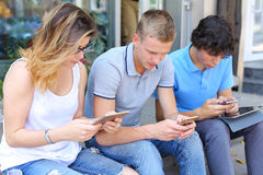 Young three friends sitting floor in the street, talking, using. Three friend female male sitting on the doorstep floor cafe, chatting, talking, using technology Stock Image