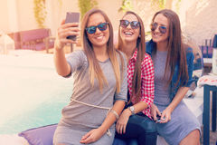 Young three girls laughing and taking selfie