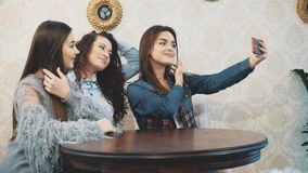 The young three good young girls are sitting in a cafe and spend time communicating. The young three good girls are sitting in a cafe and spend time stock footage