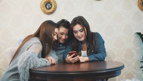 The young three good young girls are sitting in a cafe and spend time communicating. The young three good girls are sitting in a cafe and spend time stock video footage