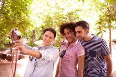 Young threesome posing for a selfie. Young threesome looking and smiling at a camera to take a selfie in the dappled shade some trees wearing casual clothing Stock Image