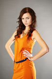 Beauty girl in orange dress. Young, tiny beautiful model posing in studio for fashion and portrait photos stock photos