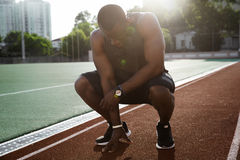 Young tired african male athlete finished running. And resting while sitting on a racetrack royalty free stock photos