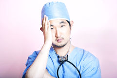 Young tired Asian surgeon wearing scrubs and looking stressed Royalty Free Stock Photos