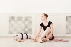 Ballerina puts on pointe ballet shoes,. Young tired ballerina in ballet studio, sit in pointe ballet shoes on floor stock photo