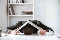 Young tired businessman lies on table with laptop stock photography