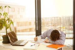 Young tired businessman sleeping at the office desk. Young tired businessman sleeping at the desk in office Stock Images