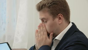 Young tired businessman working in his office in front of the laptop computer looks exhausted and worn out. In this stock footage you can see young successful stock footage