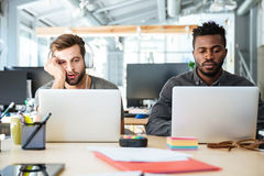 Young tired colleagues sitting in office coworking Royalty Free Stock Photo