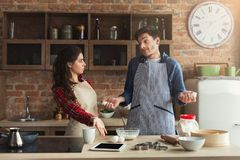 Young tired couple baking in loft kitchen. Young tired couple baking pie and having problems in loft kitchen. Young family cooking at home, using digital tablet stock photography
