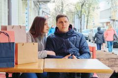 Young tired couple with shopping bags in street cafe, waiting for cup of coffee and tea. Young tired couple with shopping bags in spring street cafe, waiting for royalty free stock image