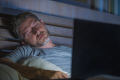 Young tired and exhausted internet or work addict man sleeping while networking late night with laptop on bed in overwork or stock photos