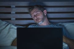 Young tired and exhausted internet or work addict man sleeping while networking late night with laptop on bed in overwork or stock images