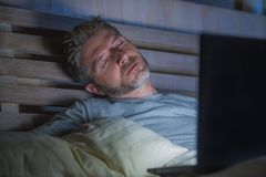 Young tired and exhausted internet or work addict man sleeping while networking late night with laptop on bed in overwork or royalty free stock photo