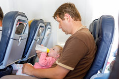 Young tired father carry his baby daughter during flight on airplane. Royalty Free Stock Images