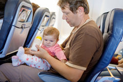 Young tired father and his crying baby daughter during flight on airplane going on vacations Royalty Free Stock Photo