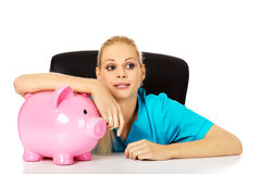 Young tired female doctor or nurse sitting behind the desk and holding a piggybank Stock Images