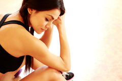 Young tired fit woman sitting on the floor Royalty Free Stock Photos