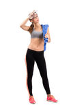 Young tired fitness woman wiping sweat from forehead with cool water bottle Stock Photo