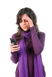 Young tired and with headache, reading a sms. On her cellphone, isolated on white background stock photography