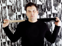 Young tired man in black shirt stands with bat on shoulders Royalty Free Stock Images