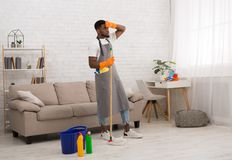 Young tired man cleaning home floor with mop. Exhausting housework. Tired african-american man cleaning home floor with mop, wiping his forehead, copy space royalty free stock images