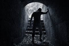 Young tired man leaves dark stone tunnel Royalty Free Stock Photo