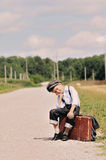 Young tired traveller sitting on the road Royalty Free Stock Photos