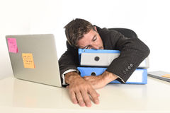 Young tired and wasted businessman working in stress at office laptop computer sleeping exhausted Royalty Free Stock Photography