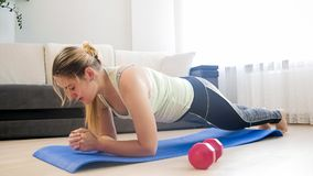 Young tired woman doing plank exercise on fitness mat at home stock photos