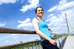 Young tired woman rest after run in the city over the bridge. Royalty Free Stock Images