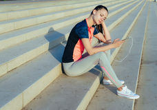 Young tired woman runner relaxing afret work out,listening music Stock Photography