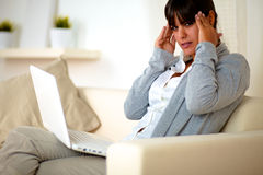 Young tired woman sitting on sofa with headache. Portrait of a young tired woman sitting on sofa with headache in front of her laptop at home Stock Photography