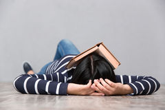 Young tired woman sleeping with book on her face Stock Image