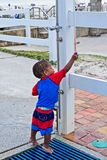 A toddler attempts to shower off at an outdoor shower at the beach. A young toddler attempts to shower off at an outdoor shower at the beach Royalty Free Stock Photography