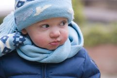 Young toddler in blue. A young toddler looking sideways all dressed in blue wearing a warm jacket and a woolly hat and scarf, outside on a cold day Stock Image