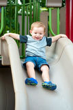 Young toddler boy child playing on slide. At playground outdoors during summer Royalty Free Stock Photos