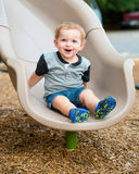 Young toddler boy child playing on slide. At playground outdoors during summer Stock Photos